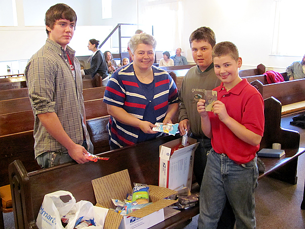 Members of Emmanuel Bible Baptist Church in Plymouth display some of the items they are gathering to send to service men and women in Iraq and Afghanistan. From left are Tim Whitaker, Amie Knight, Isaac Knight and Caleb Knight. Buy Photo