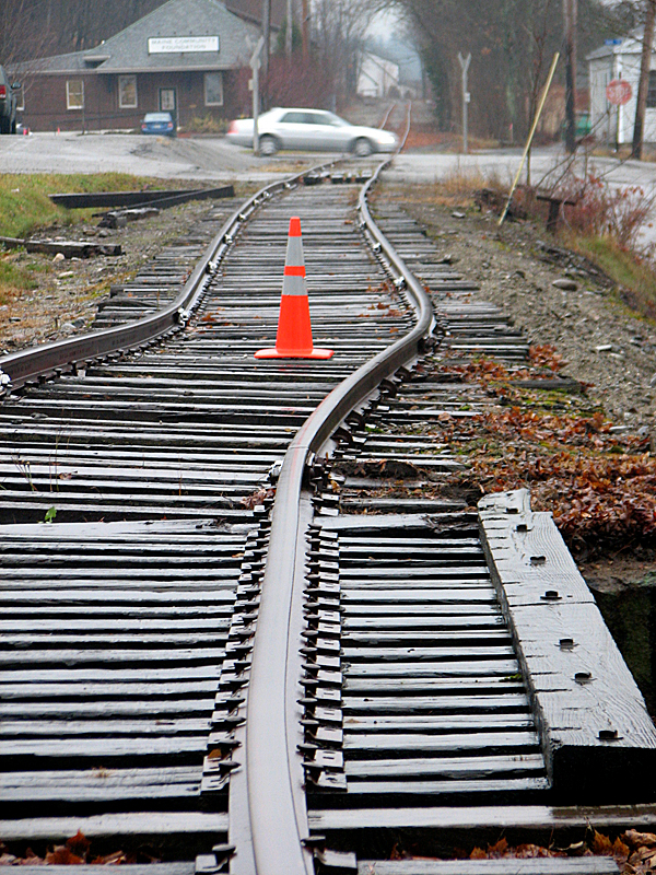 Train tracks in Ellsworth shift dramatically to the east (foreground) after a Fairpoint truck driving underneath the tracks on Monday rammed the bottom of a trestle that runs over Church Street. The truck sustained $4,000 in estimated damage and the street was closed until the tracks can be shifted back into place. According to local police, tall vehicles run into the bottom of the trestle several times a year.
