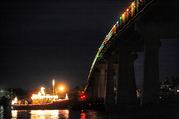 Joining nine other lobster boats and one dragger, the lobster boat &quotPriscilla D&quot owned by David Look of Jonesport and piloted by his son-in-law Colin Alley, makes its way under festively lit Jonesport-Beals Island Bridge over  Moosabec Reach Sunday evening, November 29, 2009.