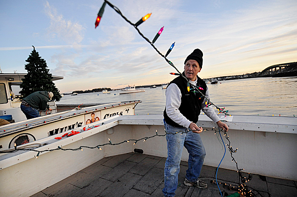 A few hours before joining the holiday flotilla on Moosabec Reach Sunday evening, November 29, 2009, Buzz Carver of Beals Island strings lights aboard his lobster boat &quotNoah's Ark&quot moored in Jonesport. He named his boat after his six-year-old son, Noah Carver.