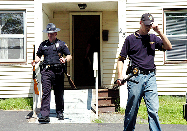 Law enforcement officials including Milo police Officer David Henderson (left) and Brownville Police Chief Nick Clukey remove seized firearms from the home of Milo resident David Krueger, 37, who was arrested Tuesday morning after a nearly nine-hour standoff with police. Krueger was charged with terrorizing, possession of a firearm by a felon and creating a police standoff. No one was injured during the incident.