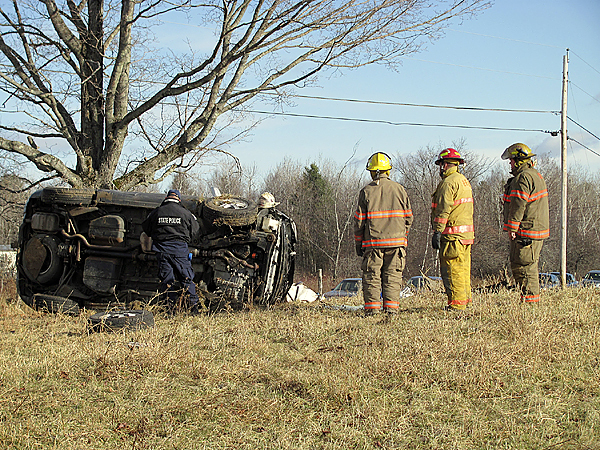Pittsfield firefighters look on as a state trooper tries to reconstruct what happened this morning to cause a crash that killed Jeffrey Guilford, 56, of Palmyra. (Bangor Daily News photo by Christopher Cousins)