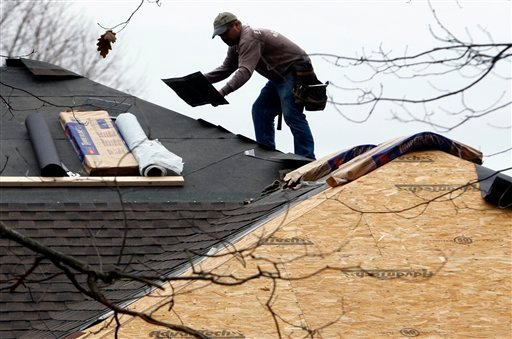 In this Nov. 24, 2009 photo, Brian Plourde of Easy Living Homes puts shingles on a roof of a home in Yarmouth, Maine. Construction spending posts tiny gain in October, led by huge rise in residential activity.(AP Photo/Robert F. Bukaty)