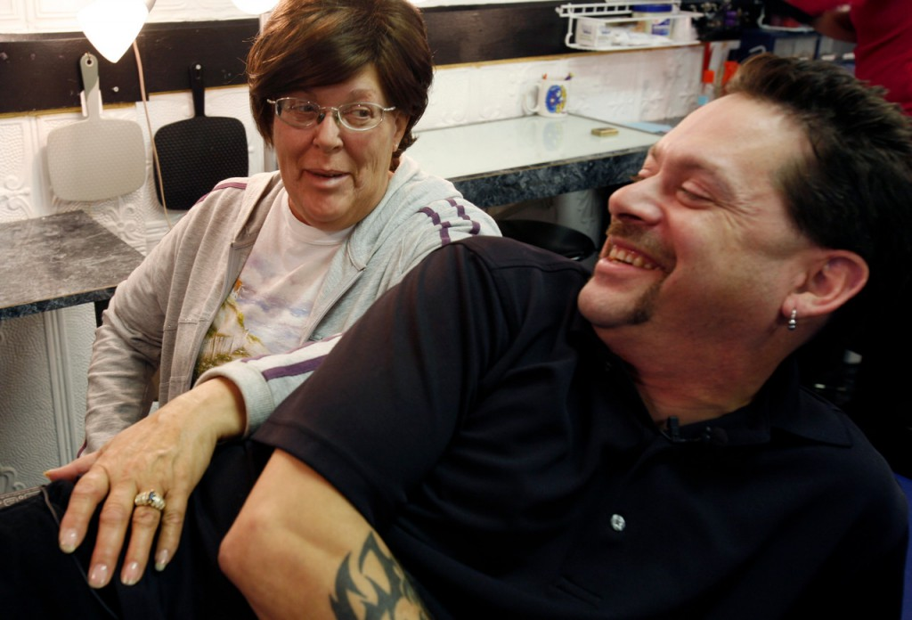 John Conway, of Windsor, Maine, shares a light moment with his mother, Mary Rapose, of Owl's Head, Maine, after getting a tattoo in the shape of a pink ribbon that is the icon for breast cancer at a shop in Augusta, Maine, on Wednesday, Dec. 2, 2009. Mary Rapose, has been diagnosed with breast cancer and family members are showing their support by getting tattoos with the classic pink ribbon icon.(AP Photo/Pat Wellenbach)