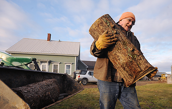 David Eccleston of Kenduskeag puts a large piece of wood on the top of smaller ones as he loads his outdoor boiler Tuesday afternoon.  While a lot of people have some issues with their firewood that didn't dry due to the large amount of rain this Summer, Eccleston said he has not noticed any problems.  (Bangor Daily News/Gabor Degre)
