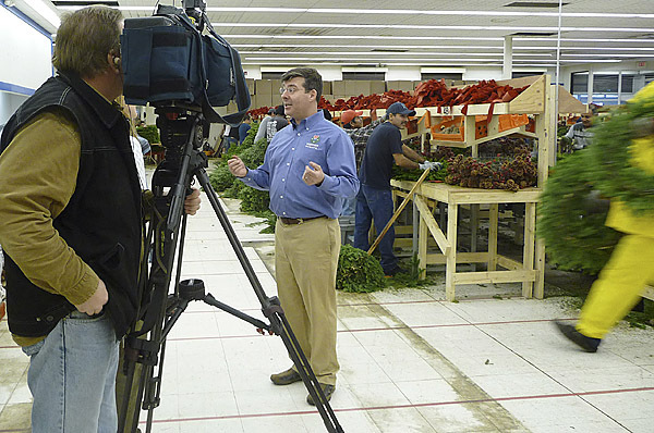 FOX News arrived in Machias Thursday for a two-day stay and remote broadcasts about the county's wreath industry and Whitney's Originals, which is the world's largest balsam fir wreath maker. David Whitney, in front of the camera, explained his business, which employs more than 400 local people as tippers, wreath or centerpiece makers, truck drivers or shippers, at nine different locations throughout Washington County. FOX News interviewed Whitney and several of his employees and today will conduct live broadcasts at 9:50 and 11:30 a.m., and 1 and 3 p.m. &quotThis will be the feel good story of the day Friday,'' Whitney said. The interviews are a part of a FOX series that focuses on companies that are growing despite a struggling economy. The series of remote broadcasts will end with a dinner that Whitney is providing for all his employees. &quotWe're serving lobster, to support that industry, blueberry pie, to support the blueberry industry, potatoes for Maine potato farmers, and steak,'' Whitney said. Whitney sells his decorated wreaths direct or through QVC shopping network and L.L. Bean. (Bangor Daily News photo by Sharon Kiley Mack)