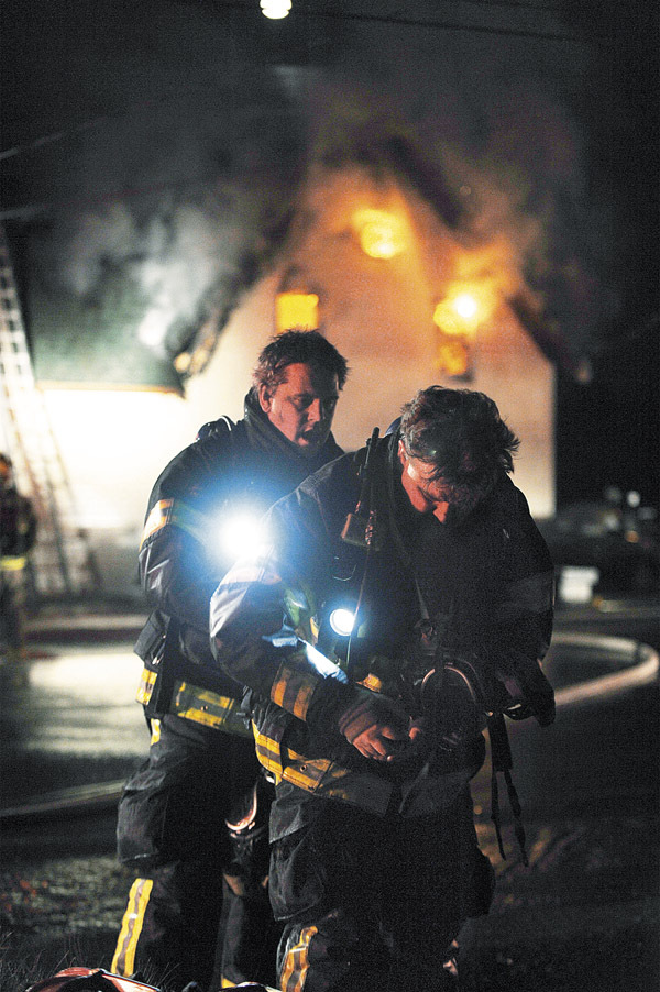 Levant firefighter, Lt. Steve Burgess, left, changes an air pack on fellow Levant firefighter Lt. Steve Burgess at the scene of a house fire on Rt.69 in Carmel on Thursday, December 3, 2009.  (Bangor Daily News/Kevin Bennett)