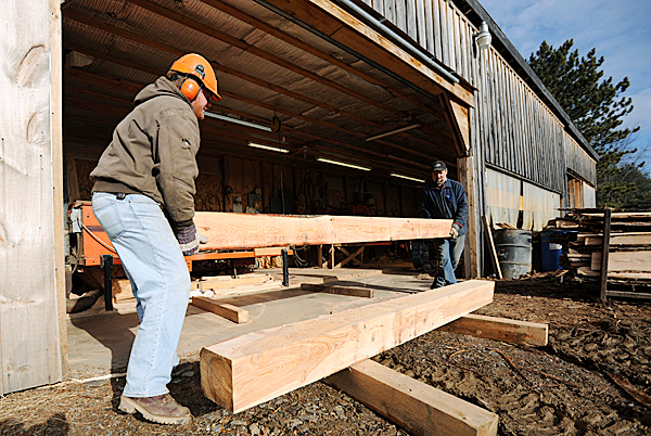 Melvin Yoder, left and David McLaughlin move a freshly-sawn hemlock beam from the milling area at Yoder's sawmill in Corinna on Tuesday, December 1, 2009. Yoder has made an offer to supply lumber to Raymond Brouillet, a homeless man from Templeton, Mass., who was evicted after building a wooden shack on town-owned property. (Bangor Daily News/Kevin Bennett)