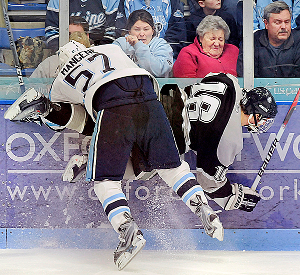 Maine's Matt Mangene, (57), checks Providence College's John Cavanagh, (16), into the boards hard enough for the front row to flinch in the first period of their game in Orono, Maine, Friday, Dec. 4, 2009.