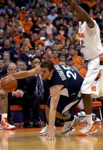 Maine's Murphy Burnatowski (25) loses his footing while driving against Syracuse's Kris Joseph during the first half of an NCAA college basketball game in Syracuse, N.Y., Saturday, Dec. 5, 2009. (AP Photo/Kevin Rivoli)