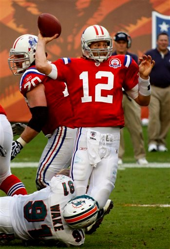 New England Patriots quarterback Tom Brady (12) is taken down by Miami Dolphins linebacker Cameron Wake during the fourth quarter of an NFL football game Sunday, Dec. 6, 2009 in Miami. Brady released the ball and it was intercepted by Miami Dolphins linebacker Channing Crowder (not shown) The Dolphins went on to win 22-21. (AP Photo/Wilfredo Lee)