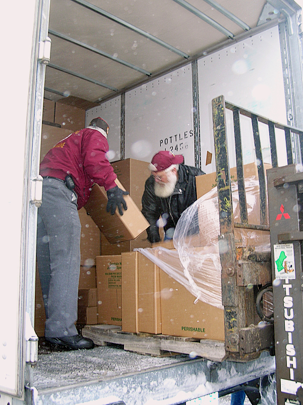Volunteers Kevin Woodward and Bruce Ebel load the last of the boxed wreaths into a tractor trailer, part of the convoy that left Worcester Wreaths in Harrington on Sunday carrying wreaths that will be placed on the gaves of America's war dead at Arlington National Cemetery.  BANGOR DAILY NEWS PHOTO BY RICH HEWITT