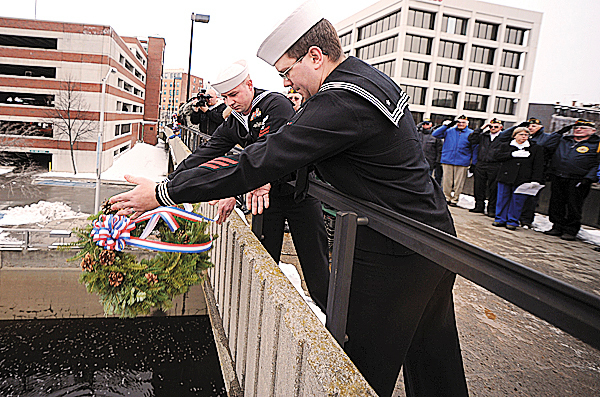 Members of the Navy Operational Support Center in Bangor, Petty officer 3rd Class Ryan Pelkey, foreground, and Petty Officer 2nd Class, Arthur Ullmann drop a wreath from the footbridge over the Kenduskeag Stream in downtown Bangor on Monday, December 7, 2009, as part of the observance of the 68th anniversary of the Japanese bombing of military bases in the Hawaiian islands in 1941.