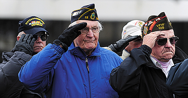 Vietnam veteran Reggie Moors Sr., left, of Bangor, along with WWII veteran William Deering, center, of Bangor, and fellow WWII veteran Lawrence Salisbury, right, of Otis, salute the flag as  the national anthem is played by the Bangor High School Band during the observance of the 68th anniversary of the Japanese bombing of military bases on the Hawaiian islands.