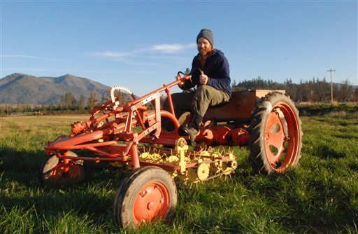 Chris Jagger shows off the Allis-Chalmers Model G tractor he converted to electric drive on his Blue Fox Farm near Applegate, Ore., on Nov. 30, 2009. A small but growing number of organic farmers have been converting the tractors, which are well suited to small farms. (AP Photo/Jeff Barnard)