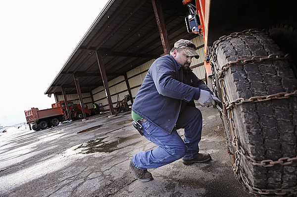Torrey Rudge (cq), a sign tech and plow truck driver for Bangor Public Works, secures chains to one of the department's truck tires Tuesday afternoon, December 8, 2009 at BPW's facility off Maine Avenue to ready it for the forecasted Wednesday snow storm. The National Weather Service has issued a storm watch in effect in northern Maine from Wednesday afternoon through Thursday Morning. (BANGOR DAILY NEWS PHOTO BY JOHN CLARKE RUSS)