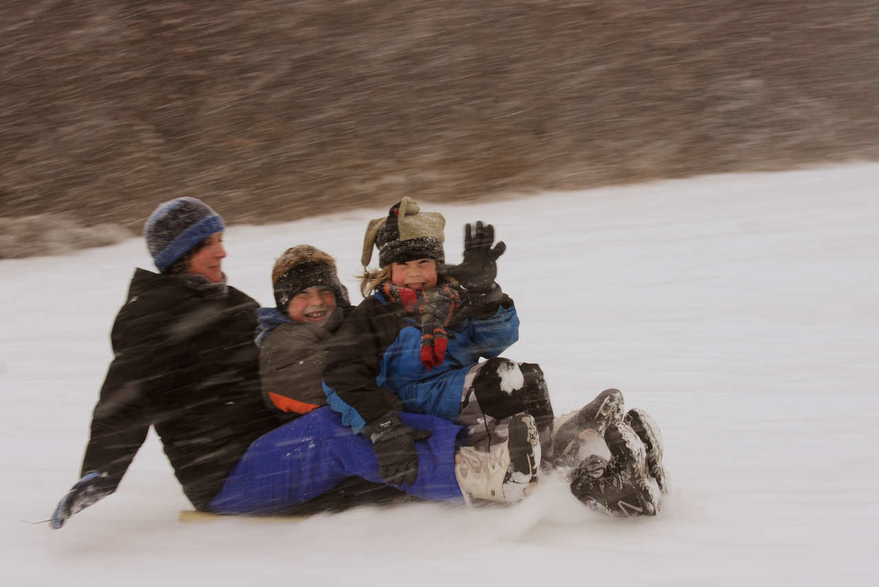 Mary Glickman, left, and her two sons, Casey, 9 and Arlo (right), 7, greet passersby as they take advantage of Wednesday's snow day off from school to ride the hill next to Asa C. Adams Elementary School in Orono early Wednesday afternoon, December 9, 2009. The boys are students at the school. The National Weather Service predicted over a foot of snow in certain parts of northern Maine. (Bangor Daily News/John Clarke Russ)
