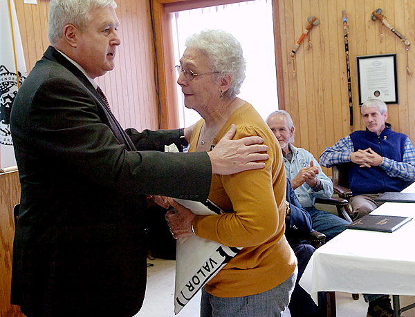 Senior Pentagon Army official Danny Pummill embraces Jean Chavaree after presenting her with a flag in honor of her brother Donald Francis' service in WWII, during a ceremony recognizing veterans at the Penobscot Community Center on Indian Island on Thursday, Dec. 10, 2009.