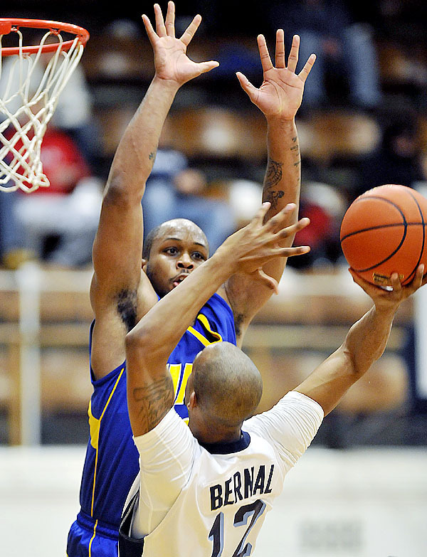 UMPI's Ray Mitchell gets two hands in the face of Maie's Junior Bernal, (12), in the first half of their game in Orono, Maine, Thursday, Dec. 10, 2009.