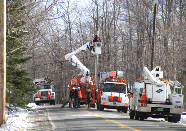 Line workers repair power lines Saturday on Route 151 in Hartland after a single-car accident. Buy Photo