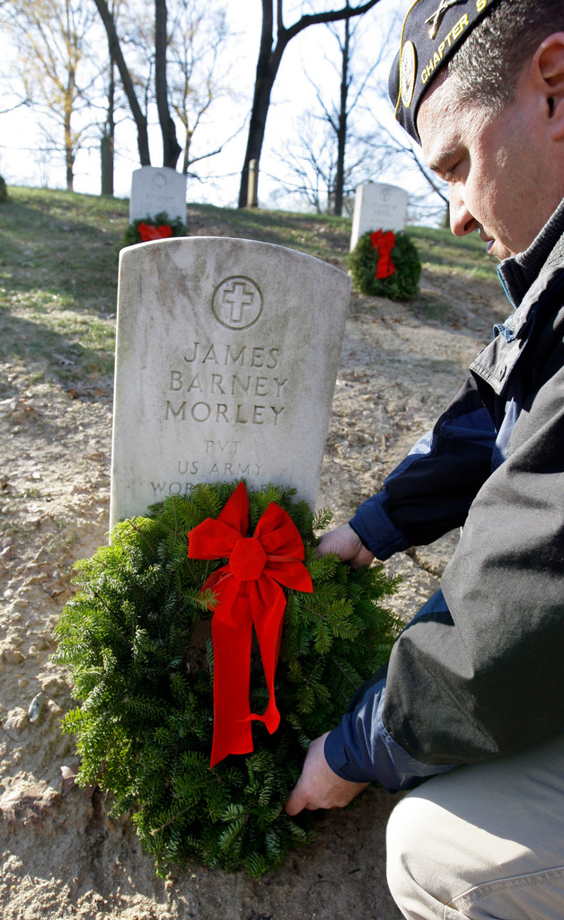 Tim Howe, of Warwick, R.I., a former Army staff sergeant now a member of the Disabled American Veterans Chapter 9, places a wreath Saturday as part of Wreaths Across America at Arlington National Cemetery in Arlington, Va.