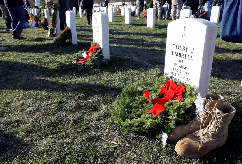 A wreath and a pair of boots adorn a grave Saturday in Section 60 at Arlington National Cemetery  in Arlington, Va. More than 16,000 wreaths were placed at graves throughout the cemetery.