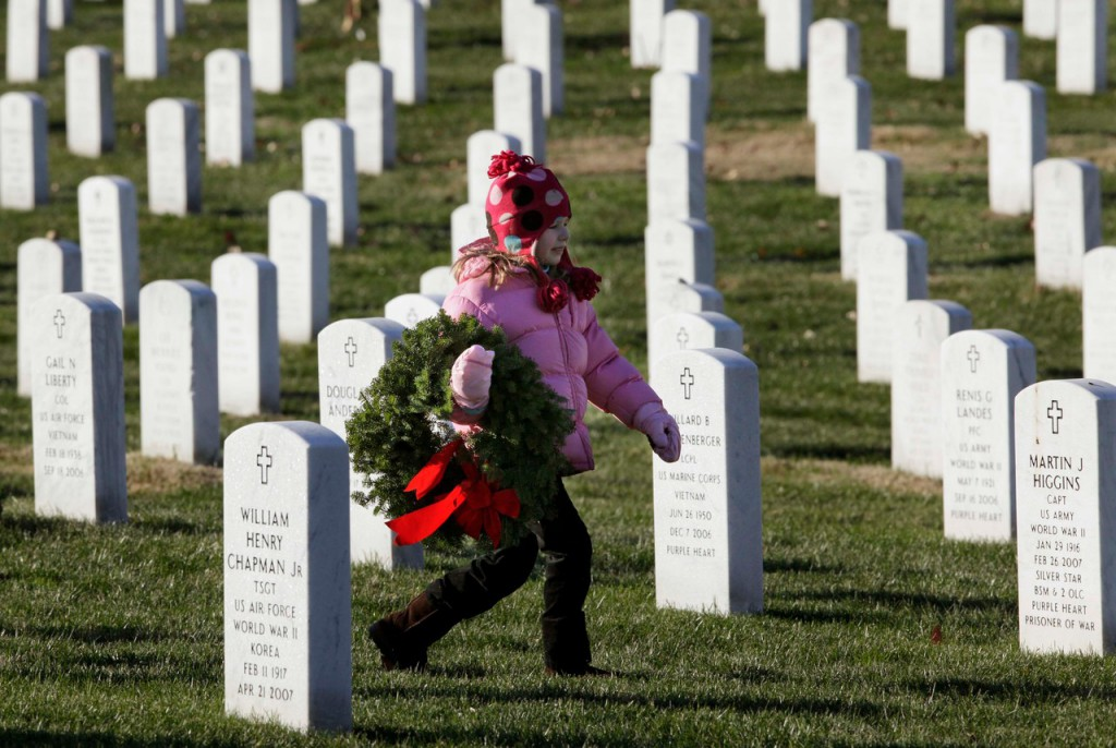Emily Mead, 6, of Great Falls, Va., walks to a relative's grave with a wreath Saturday as part of Wreaths Across America in Section 60 at Arlington National Cemetery in Arlington, Va.