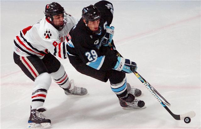 University of Maine junior Tanner House (29) controls the puck ahead of Northeastern sophomore J.P. Maley in the first period of Saturday's game at the Alfond Arena in Orono. Buy Photo