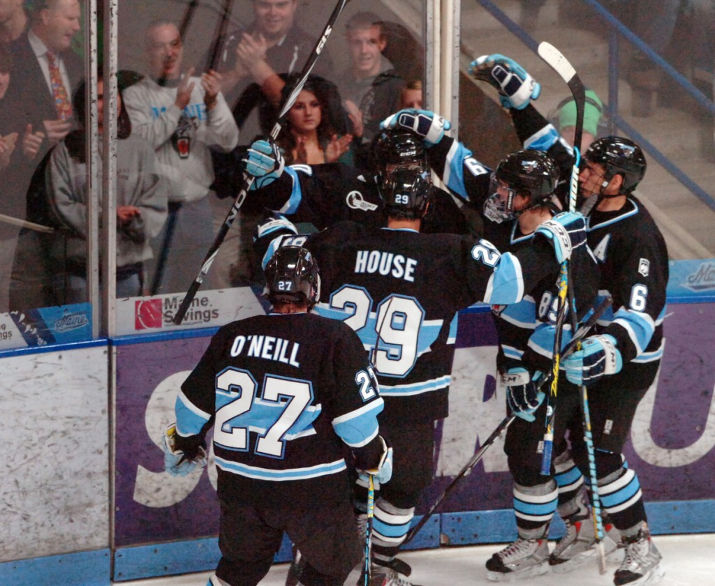 The University of Maine Black Bears celebrate their third goal against Northeastern scored by sophomore Brian Flynn in the second period of Saturday's game at the Alfond Arena in Orono. Buy Photo