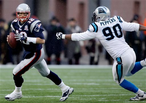 New England Patriots quarterback Tom Brady (12) scrambles as he tries to elude Carolina Panthers defensive end Julius Peppers (90) during the first half of an NFL football game in Foxborough, Mass., Sunday, Dec. 13, 2009. (AP Photo/Charles Krupa)