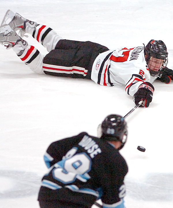 Northeastern's Alex Tuckerman (top) fails to control the puck against the University of Maine's Tanner House in the second period of Saturday's game, Dec. 12, 2009 at the Alfond Arena in Orono. Maine won 5-1. (Bangor Daily News/Bridget Brown)