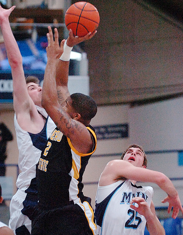 The University of Maine's Mike Allison (left) and Murphy Burnatowski (right) defend against Kennesaw's Markeith Cummings in the first half of Sunday's game, Dec. 13, 2009 at the Alfond Arena in Orono. (Bangor Daily News/Bridget Brown)