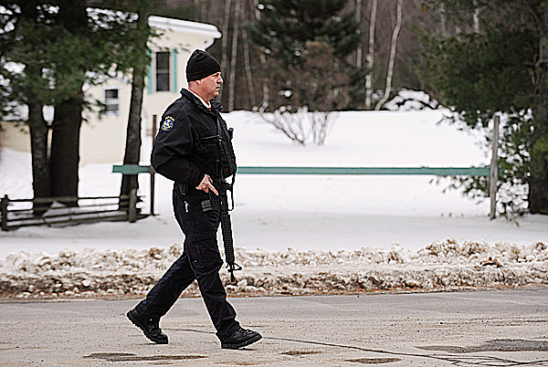 A Maine State Police trooper watches over the intersection of Southgate Road and Rt. 16 in Old Town on Sunday, December 13, 2009 after a report of shots being fired in the area. A K-9 unit was called in to search the woods behind a house on Southgate Road.