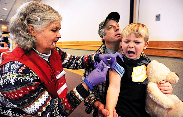 Registered nurse Kathy Lena, left, gives five-year-old Brad Goulette of Milo an H1N1 shot as he is being held by his father, Greg, on Monday, December 14, 2009 during an immunization clinic at the Bangor Civic Center.