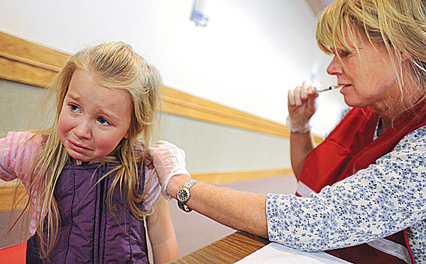 Emma Seeley, 5, of Brewer gets her H1N1 shot from registered nurse Nancy Gray during an immunization clinic held on Monday, December 14, 2009 at the Bangor Civic Center.