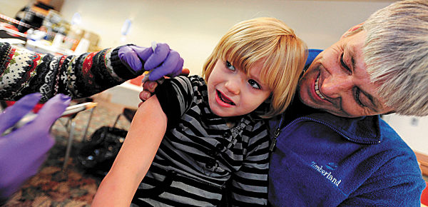 Amanda Spencer, 6, of Dedham gets her H1N1 shot while being held by her father, Richard, during an immunization clinic at the Bangor Civic Center on Monday, December 14, 2009.