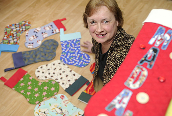 Lilly Weatherbee shows some of the 100 holiday stockings that she has been sewing since January at her home in Dover-Foxcroft. She will give them to Manna Ministries Inc. in Bangor and they will be distributed to area needy people over the holidays.  BANGOR DAILY NEWS PHOTO BY JOHN CLARKE RUSS