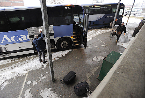 Chuck Lee,right, of Chicago, IL approaches an Acadian Line bus as the coach driver (who wished to remain unidentified) opens the luggage compartment before the bus made its daily departure from the Bangor bus terminal on Main Street at 11:45 am , bound for New Brunswick Tuesday, December 15, 2009. The Acadian Line may discontinue its overnight Bangor stop in Spring 2010.