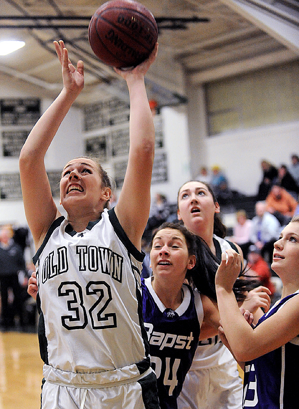 Old Town High School's Ashley Abbott (#32) puts up a shot while flanked by John Bapst Memorial High School's Brittany Williams (#24) and Taylor Edgecomb (#23, right) during the first quarter of their game at Old Town High School Thursday night, December 17, 2009. (Bangor Daily News/John Clarke Russ)