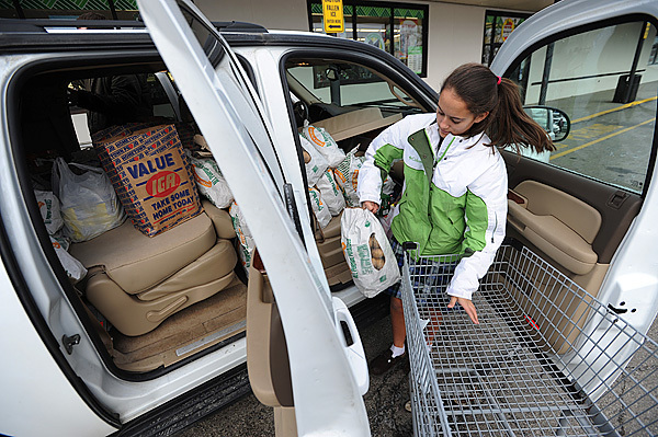 All Saints Catholic School student Kiana Yardley loads bags of potatoes into a vehicle on Tuesday, December 22, 2009 at Bell's IGA in Orono. The students were purchasing food as part of a service project to feed the hungry on Indian Island as well as stock the island's food pantry. (Bangor Daily News/Kevin Bennett)
