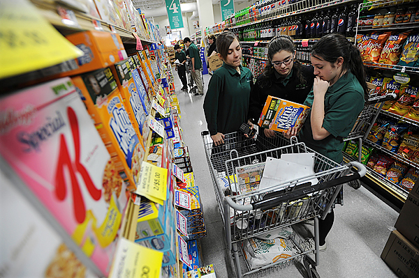 All Saints Catholic School students, Kim Shaw, left, Shannon Rose O'Connor, center, and Ellen Coddington, right, read the nutritional information on a box of cereal as they shop for food as part of a service project to feed the hungry on Indian Island as well as stock the island's food pantry. (Bangor Daily News/Kevin Bennett)