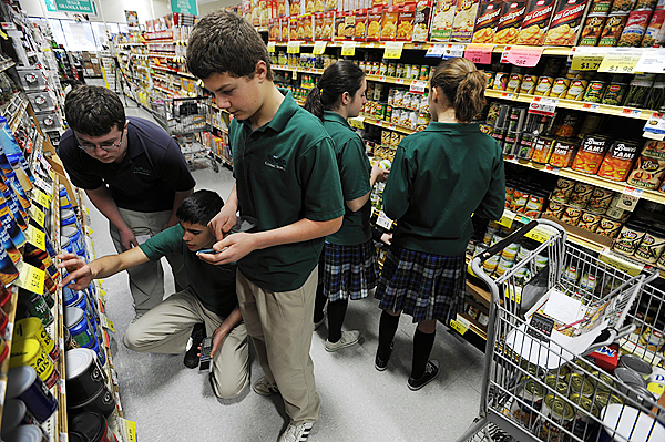 All Saints Catholic School students, Sean Yankowsky, left, Noah Potvin, second from left, and Patrick Leonard, center, calculate the cost of canned goods as Ellen Coddington, second from right, and Kim Shaw, right, do the same at Bell's IGA in Orono on Tuesday, December 22, 2009. The students were spending donated money to purchase food to feed the hungry on Indian Island and to stock the island's food panty.  (Bangor Daily News/Kevin Bennett)