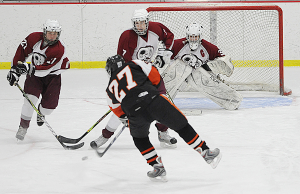 Brewer High School's Chris Lopez (#27) puts the puck past Bangor High School's Tyler Shanklin (#21), Joe Seccareccia (#7) and goalie Zach Hamilton for the team's third goal and his second in the first period of their match at Sawyer Arena in Bangor Tuesday night, December 22, 2009. (Bangor Daily News/John Clarke Russ)