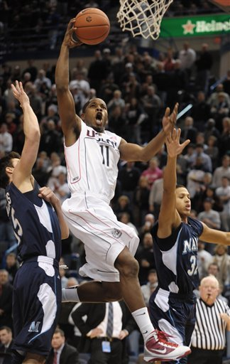 Connecticut's Jerome Dyson, center, drives to the basket while guarded by Maine's Troy Barnies, left, and Gerald McLemore, right, in the first half of an NCAA college basketball game in Hartford, Conn., Tuesday, Dec. 22, 2009.  (AP Photo/Jessica Hill)