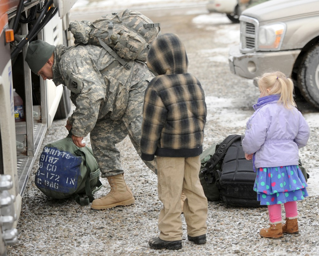Phoebe Fairservice, 2, (right) and her brother Michael, 7, watch their father Sgt. Jim Fairservice take out his bags from the bus.  Fairservice is one of about 40 soldiers from the Bravo Company 3rd Batallion 172nd Infantry unit who arrived at the Brewer Armory by bus Wednesday morning, from training in Indiana.  The unit is home for about two weeks before it deploys to Afghanistan.  A large portion of the transportation cost was paidd for by the Stephen and Tabitha King family. (Bangor Daily News/Gabor Degre)