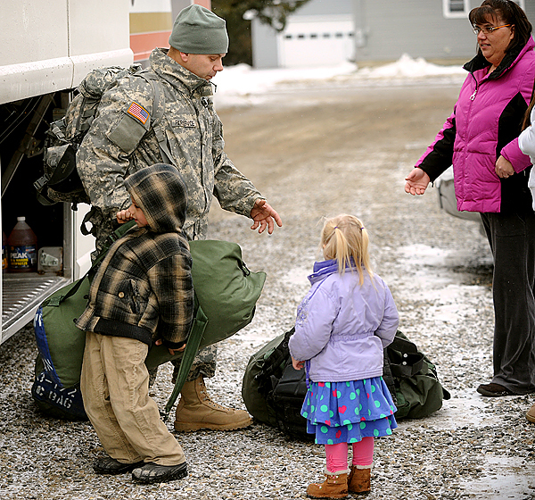 Sgt. Jim Fairservice of Gardiner gets some help from his son Michael, 7, as his daughter Phoebe, 2, and wife Christine (right) await by the bus.  Fairservice is one of about 40 soldiers from the Bravo Company 3rd Batallion 172nd Infantry unit who arrived at the Brewer Armory by bus from training in Indiana Wednesday morning.  The unit is home for about two weeks before it deploys to Afghanistan.  The large portion of the transportation was paid for by the Stephen and Tabitha King family. (Bangor Daily News/Gabor Degre)