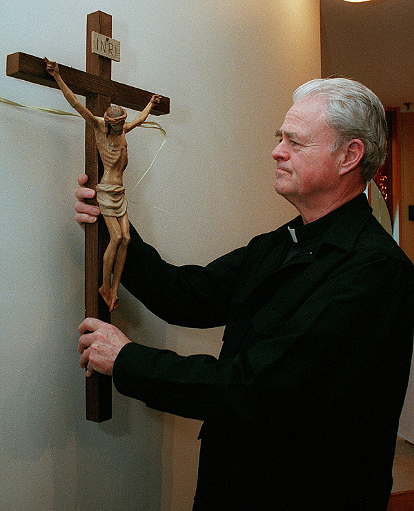 The Rev. John Austin, new chaplain at Eastern Maine Medical Center, removes the crucifix from the wall of the medical center chapel after a Tuesday afternoon Mass. The chapel is used by other denominations, so religious icons related to specific faiths are removed after services.  BANGOR DAILY NEWS PHOTO BY BOB DELONG