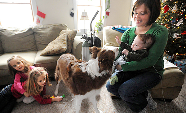 Jess Tracy holds her youngest child, five-month-old Phineas, as her daughters, Ruby,3, (left) and Lydia, 5, play at their Winterport home on Christmas eve.  Phineas was born with chronic lung disease, and also has heart and kidney problems.  After a parishioner asked the pastor of the Winterport Baptist Church to pray for the family, Jess and her husband, Ben, received a surprise visit.  Pastor Allen Gregory and members of the congregation came by with Christmas presents and gift cards to help out the family, which has had a hard time since the birth of their youngest. BANGOR DAILY NEWS PHOTO BY GABOR DEGRE