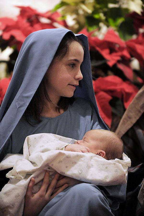 While singing &quot Away in a Manger&quot with other children,  &quotMary&quot portrayed by Michele Maybury (cq), 10 of Brewer, held the baby Jesus, played by one-month-old William Whalen of Brewer during the celebration of Christmas Eve Mass at St. Joseph's Catholic Church in Brewer Thursday evening, December 24, 2009. BANGOR DAILY NEWS PHOTO BY JOHN CLARKE RUSS