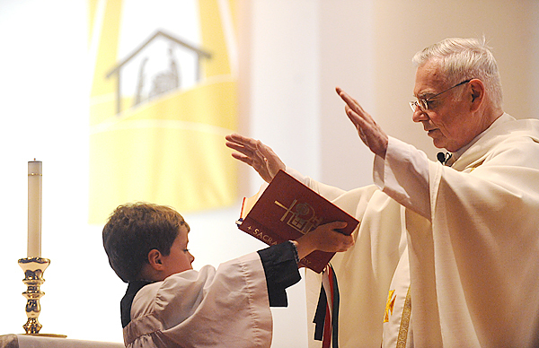 Father Roland Nadeau, chaplain at St. Joseph Hospital in Bangor, closes Christmas Eve Mass with the help of acolyte Joshua Demaso, 9, at St. Joseph's Catholic Church in Brewer, Thursday evening December 24, 2009. BANGOR DAILY NEWS PHOTO BY JOHN CLARKE RUSS